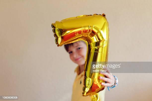 boy with number 7 shape balloon - 数字の7 ストックフォトと画像