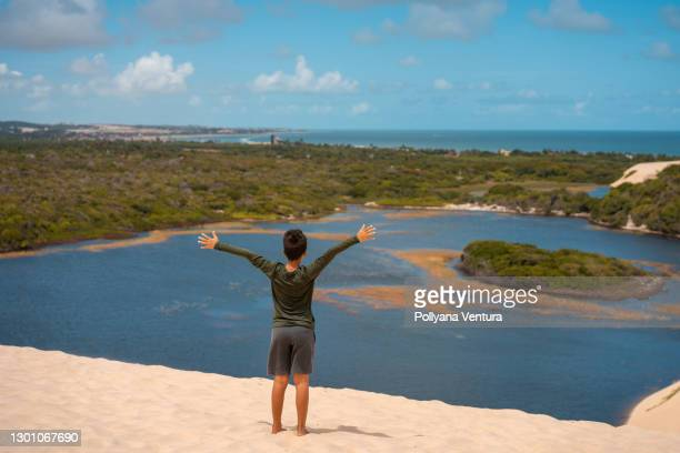 boy with open arms looking at the view of the lagoon in genipabu - natal brazil stock pictures, royalty-free photos & images