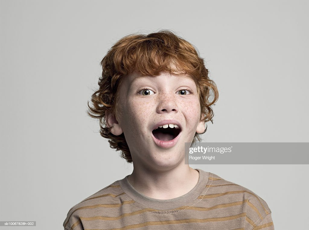 Boy (8-9 years) with open mouth, portrait, studio shot : Stock Photo