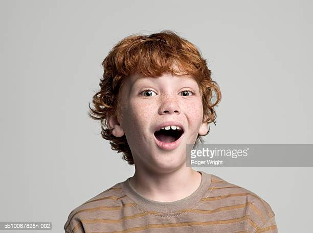 boy (8-9 years) with open mouth, portrait, studio shot - surprise stock pictures, royalty-free photos & images