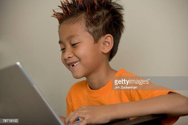 Boy with Orange Spiked Hair Using a Laptop