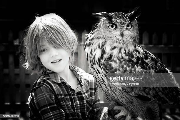Boy With Owl Standing Outdoors