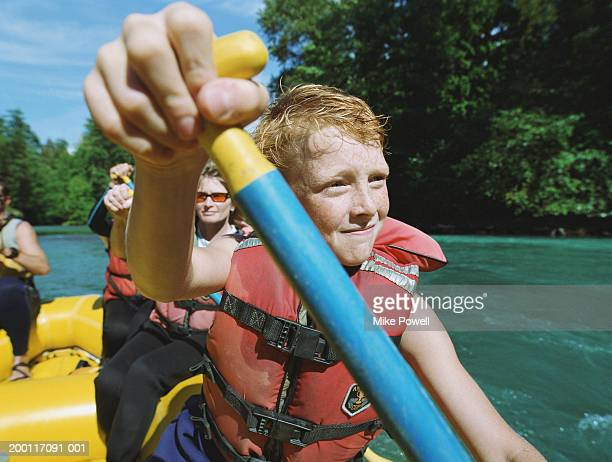 Boy (8-10) with paddle, river rafting with family