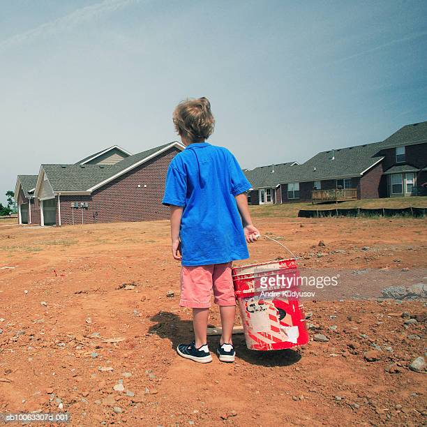 Boy (6-7) with paint bucket in front of houses, rear view
