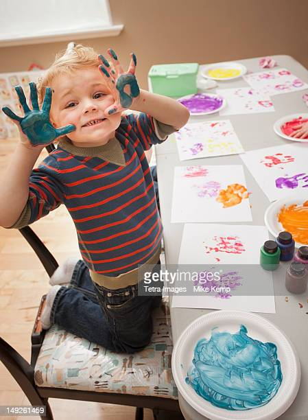 Boy (4-5) with paint covered hands