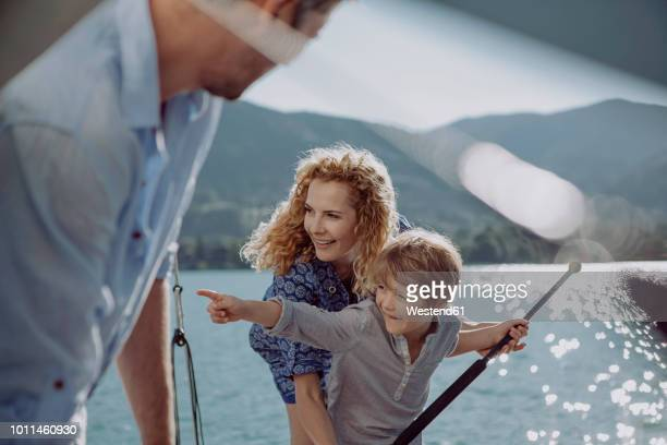 boy with parents on a sailing trip pointing his finger - variable schärfentiefe stock-fotos und bilder