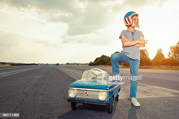 Boy with pedal car on race track