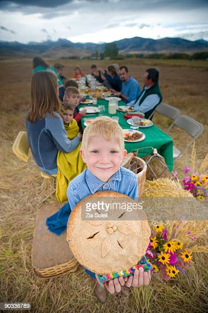 boy with pie at outdoor organic Fall dinner