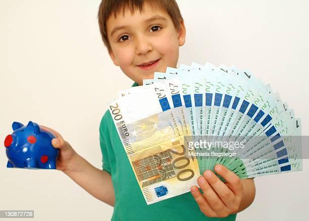 Boy with piggybank and money