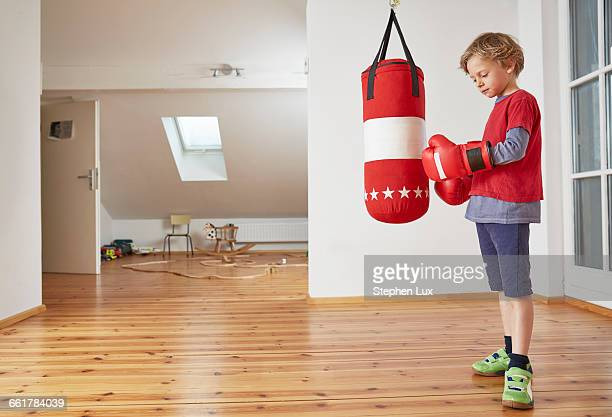 Boy with punch bag putting on boxing gloves