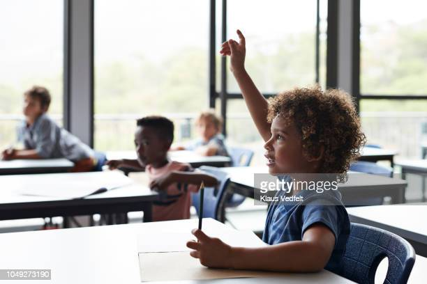 boy with raised hand in classroom - infância - fotografias e filmes do acervo