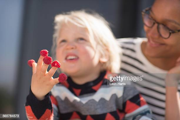 Boy with raspberries on fingers, mother watching