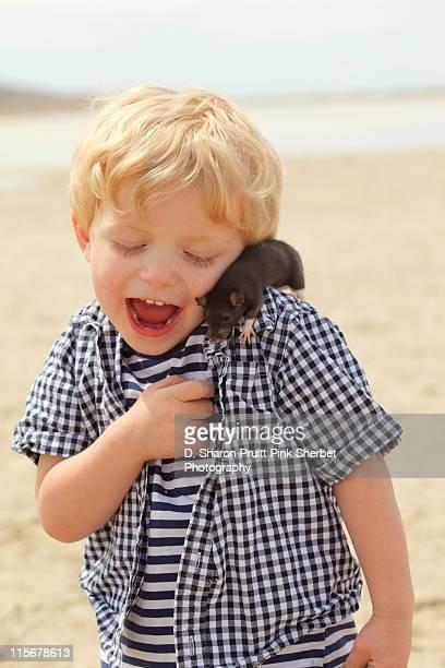 Boy with rat on beach.