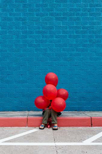 Boy With Red Balloons Sitting On Sidewalk Against Blue Wall - gettyimageskorea