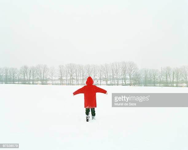 Boy with red coat walking through snow field