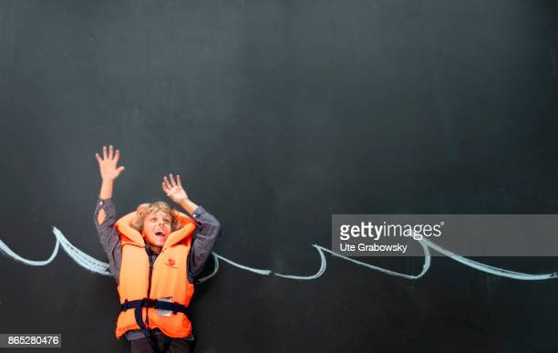 A boy with rescue vest swims in front of a blackboard in an illustrated sea and threatens to sink on August 08 2017 in Sankt Augustin Germany