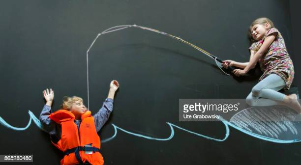 A boy with rescue vest swims in front of a blackboard in an illustrated sea and threatens to sink A girl saves him with a fishing rod on August 08...