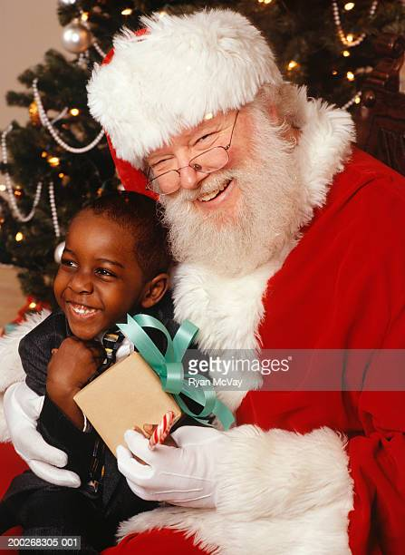 boy (3-4) with santa claus by christmas tree, close-up, portrait - santa close up stock pictures, royalty-free photos & images