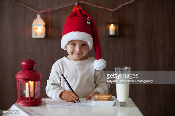 Boy with Santas hat writing letter