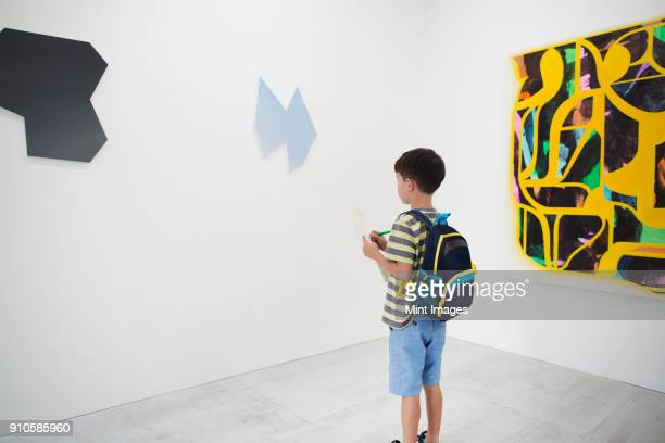 boy with short black hair wearing backpack standing in art gallery, holding pen and paper, looking at modern painting. - kunst kultur und unterhaltung fotos stock-fotos und bilder