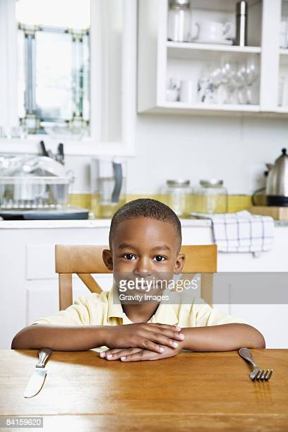 Boy with Silverwear Sitting at the Kitchen Table