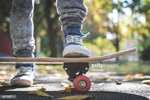 Boy with skateboard in park in autumn