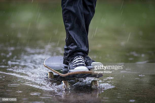 boy with skateboard in the rain. - wet jeans stock photos and pictures