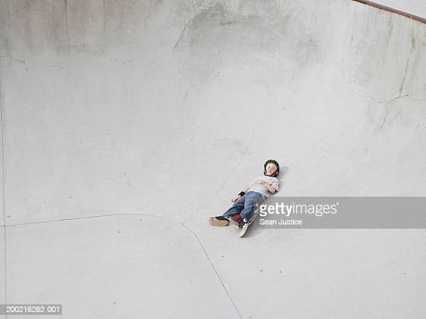 Boy (10-12) with skateboard laying on course