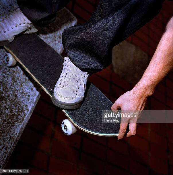Boy with skateboard on ledge, low section