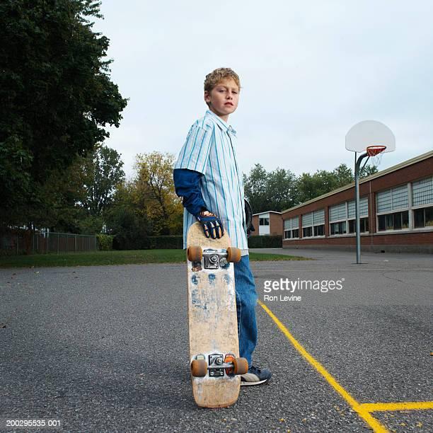 Boy (10-12) with skateboard, portrait