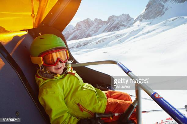 Boy with skis sitting in a chair lift