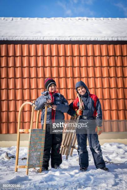 Boy with sled in front of their house on snow