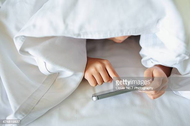 Boy with smart phone in bed.