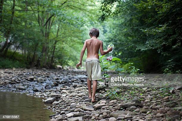 Boy with snorkel mask by stream