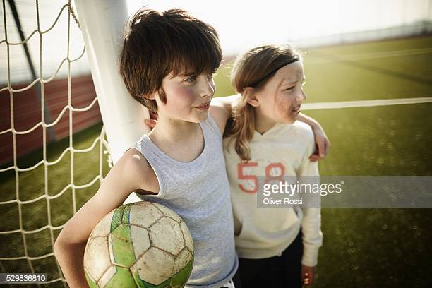 Boy with soccer ball and girl at goal