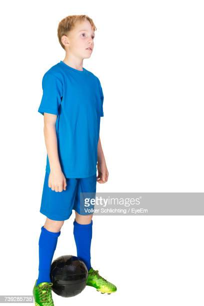 Boy With Soccer Ball Standing Against White Background