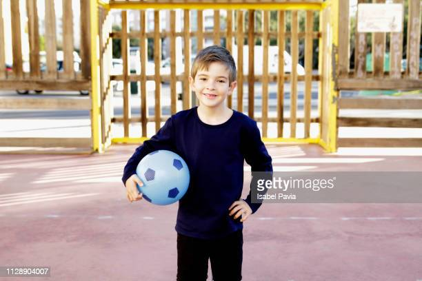 Boy With Soccer Ball Standing In Court