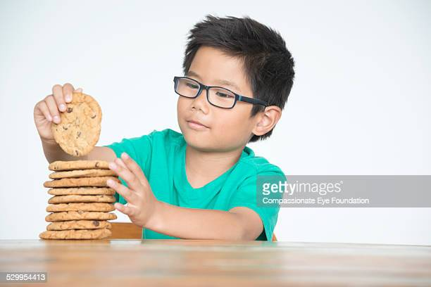 """boy with stack of cookies - """"compassionate eye"""" foto e immagini stock"""