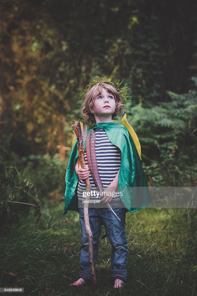 Boy (4-5) with stick and feather looking up : Stock Photo