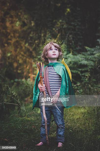 Boy (4-5) with stick and feather looking up