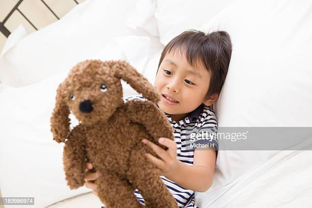 A boy with stuffed toy in his room