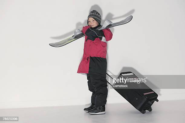 Boy with suitcase and skis
