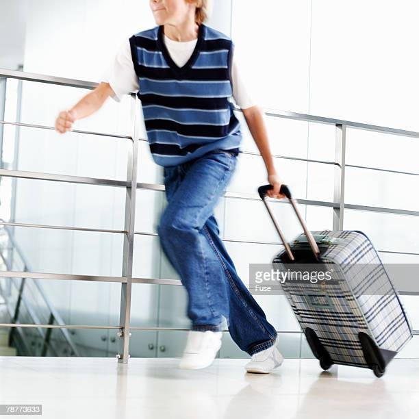 Boy with Suitcase Running in Airport