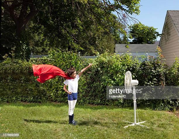 boy with superhero cape blown by fan