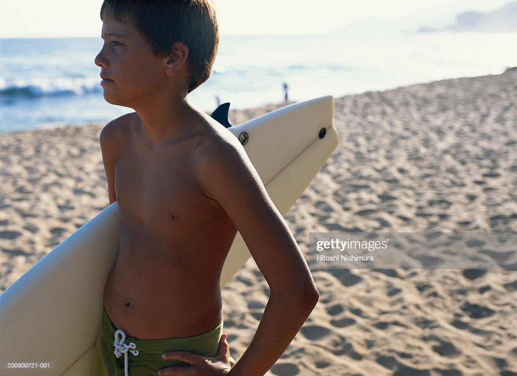 Boy (11-12) with surfboard standing at beach, looking away : Stock-Foto