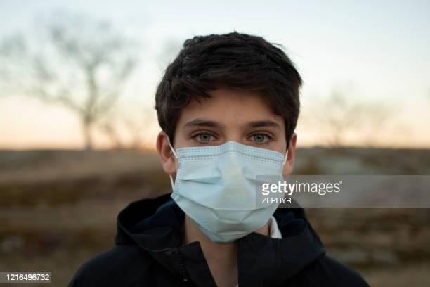 boy with surgical mask - aplanar a curva imagens e fotografias de stock