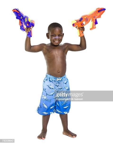 boy with swim trunks and water pistols - knaben in badehosen stock-fotos und bilder