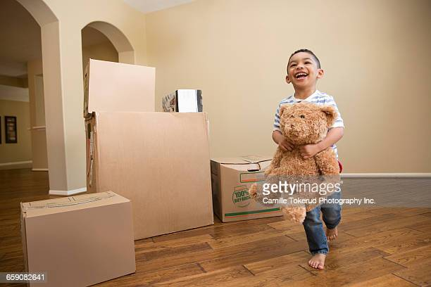 Boy with teddy bear and moving boxes