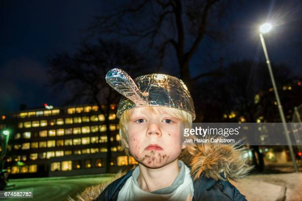 Boy with ten foil saucepan on his head