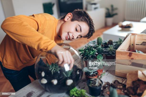Boy with terrarium at home